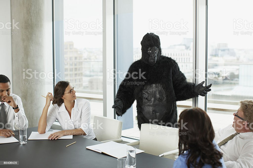 Gorilla and businesspeople having meeting in conference room royalty-free stock photo