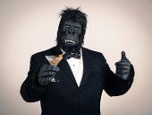 A gorilla in a tuxedo holding a martini.