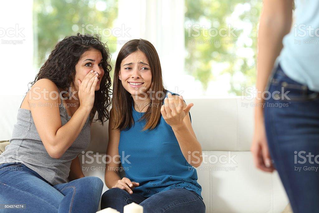 Gossip girls criticizing another woman stock photo