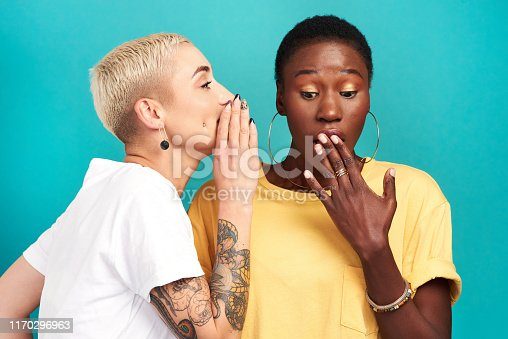 Studio shot of a young woman whispering in her friend's ear against a turquoise background