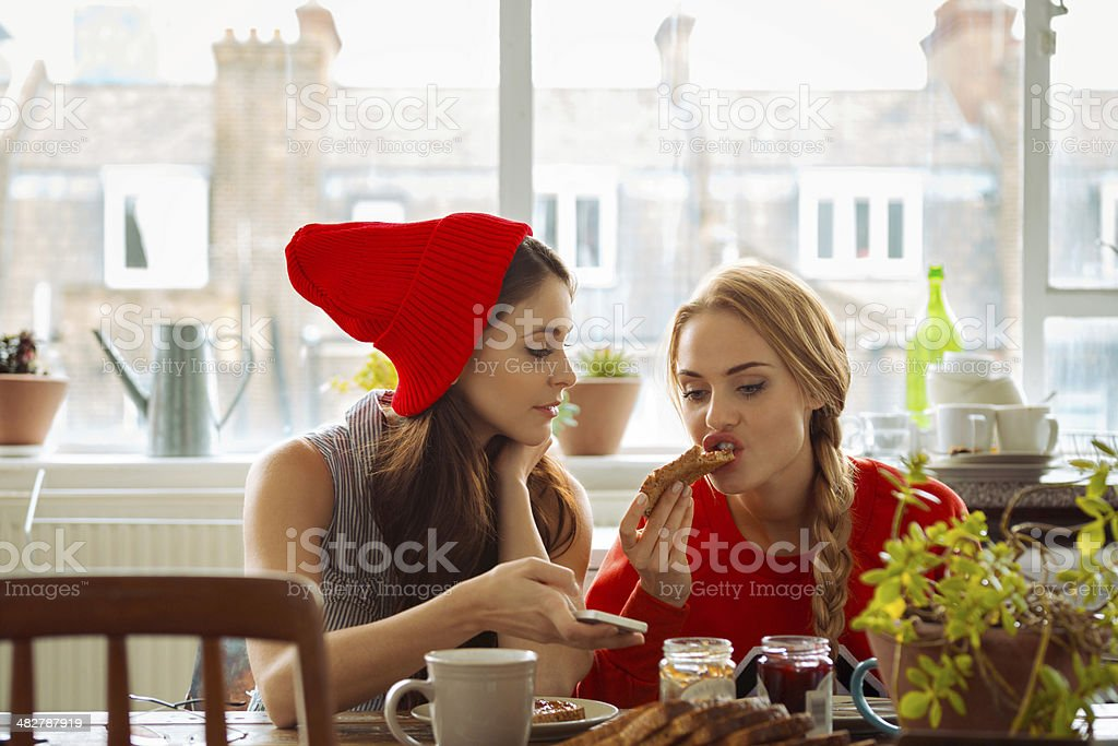 Gossips Two girls sitting at the kitchen table and talking over the breakfast. Brunette holding the smart phone in hand. 20-24 Years Stock Photo