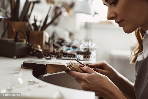 I got my inspiration. Side view of a female excited jeweler creating a silver ring at her workbench. Making accessories. Jewelry making process. Jewelry equipment. Working process. Jewelry manufacturing concept.