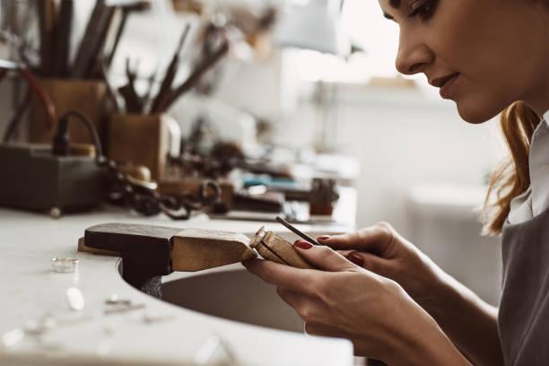 jag fick min inspiration. sidovy av en kvinnlig upphetsad juvelerare skapa en silver ring på hennes arbets bänk. göra tillbehör - hand gold jewels bildbanksfoton och bilder