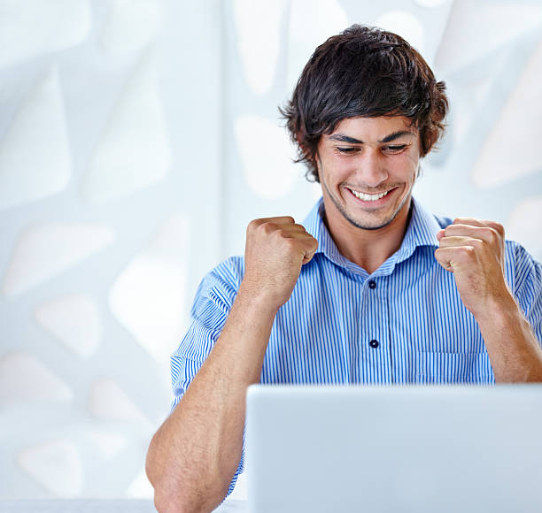 I got that promotion! Shot of an ecstatic young businessman sitting in front of her laptop perks stock pictures, royalty-free photos & images