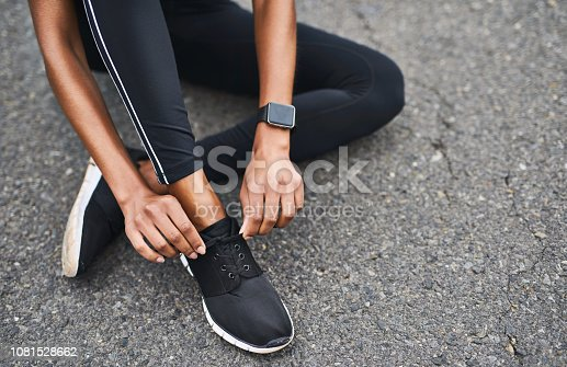 Closeup shot of a sporty woman tying her shoelaces while exercising outdoors