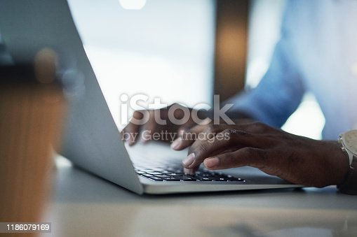 Closeup shot of an unrecognisable businessman working on a laptop in an office at night