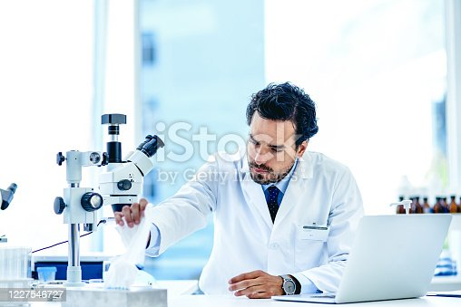 Shot of a young scientist reaching for a tissue from a tissue box in a lab