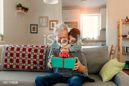 Caring grandson giving present to grandpa, attention and care for loved ones