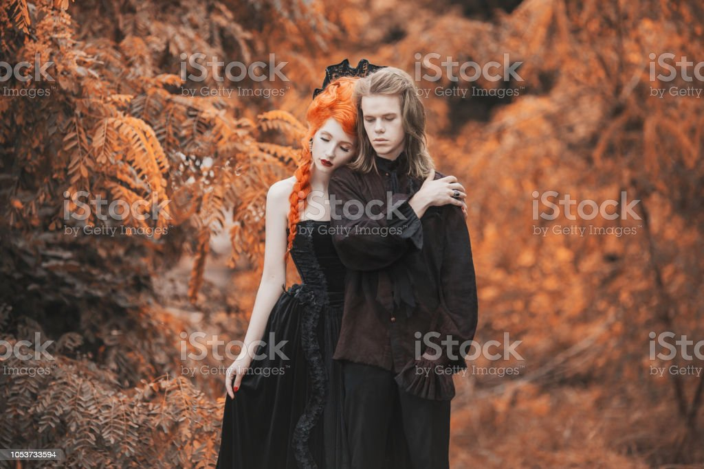 Goth couple in halloween costume. Gloomy vampire in baroque clothes. Redhead woman vampire in black baroque dress. Goth clothes for halloween party. Gloomy couple on autumn background. stock photo