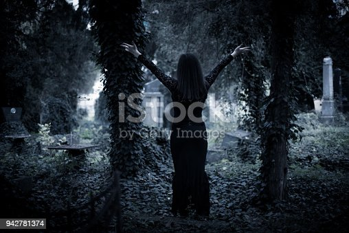 A solitary goth girl standing in an overgrown cemetery with hands stretched out