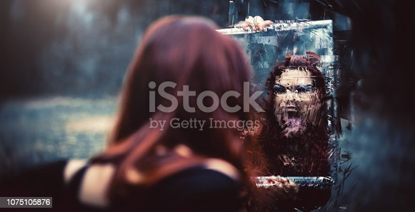 A goth girl with a mirror and her distorted reflection screaming back at her