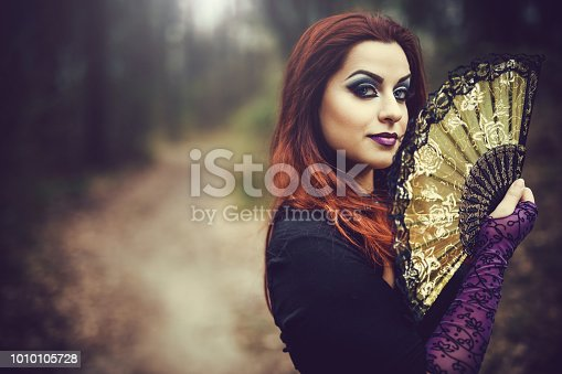 A pretty redhead goth girl holding a fan in a forest during autumn