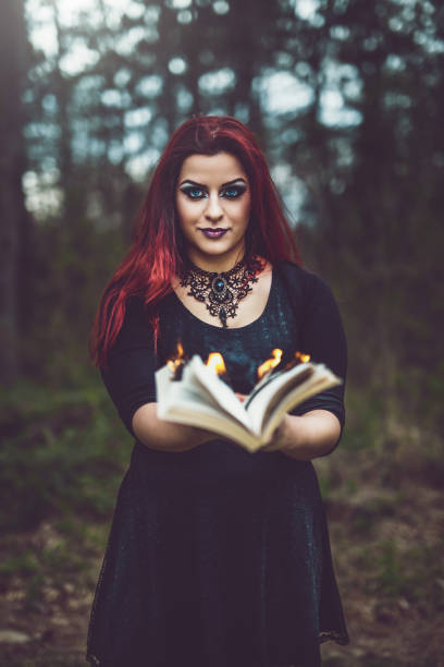Goth girl with pages ablaze A redhead goth girl holding a book with pages aflame ablaze stock pictures, royalty-free photos & images