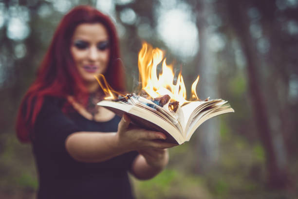 Goth girl with pages ablaze A selective focus shot of a redhead goth girl holding an open book with pages aflame ablaze stock pictures, royalty-free photos & images