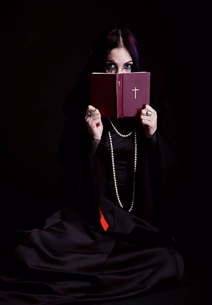 Goth-girl is reading the Bible stock photo