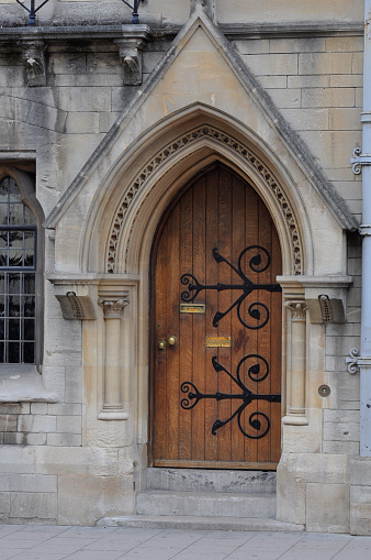 View of english gothic building facade with ogival arched wooden door and intricate architectural detailing from Oxford High Street, Oxford, United Kingdom.