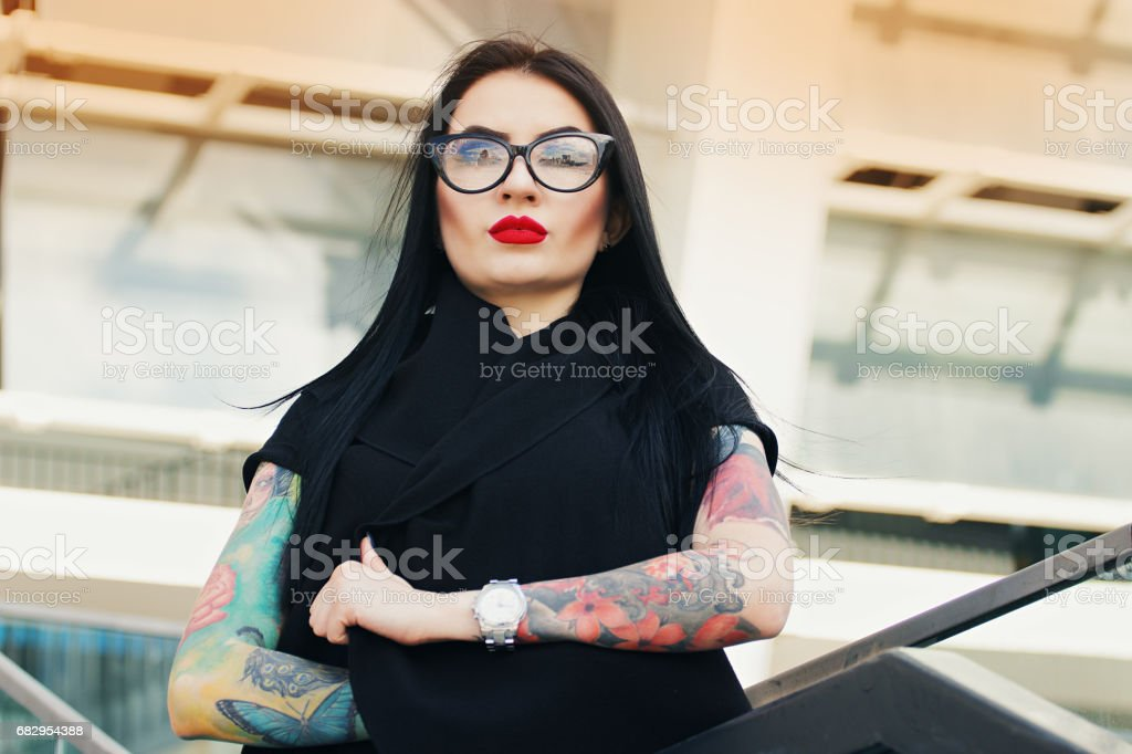 Gothic beauty. Portrait of attractive tattoed hipster girl keeping arms crossed while standing against urban background. royalty-free stock photo