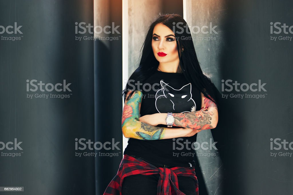 Gothic beauty. Portrait of attractive tattooed hipster girl posing to camera while standing against urban background. royalty-free stock photo