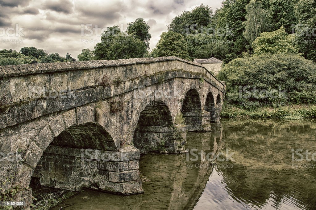 Gothic Bridge crossing shallow stream stock photo