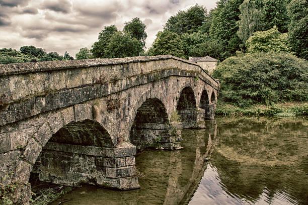Gothic Bridge crossing shallow stream stock photo