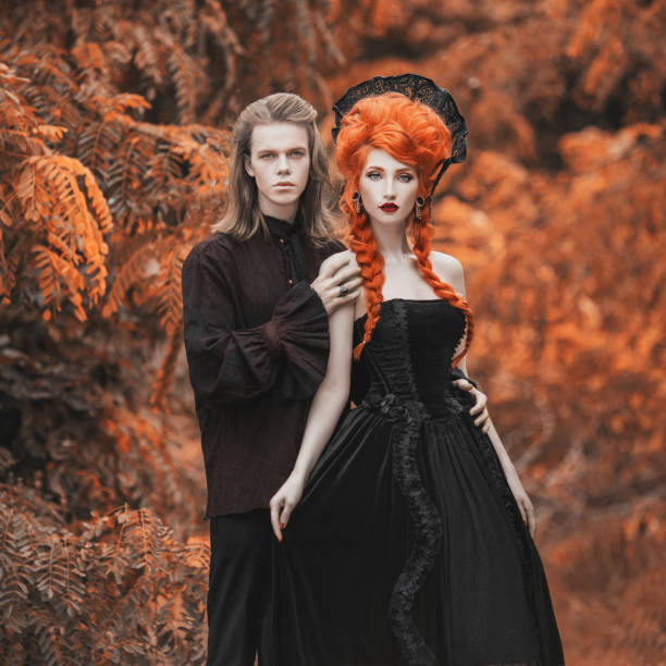 Gothic couple in halloween costume. Gloomy vampire in victorian clothes. Redhead woman vampire in black victorian dress. Gothic clothes for halloween party. Gloomy couple on autumn background. Gothic couple in halloween costume. Gloomy vampire in victorian clothes. Redhead woman vampire in black victorian dress. Gothic clothes for halloween party. Gloomy couple on autumn background. goth stock pictures, royalty-free photos & images