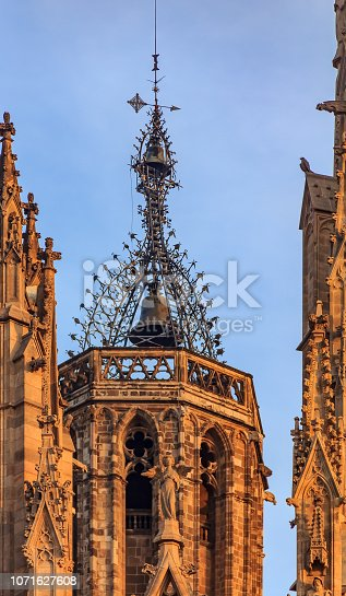 Ornate filigree gothic ironwork detail of the bell tower of Cathedral of the Holy Cross and Saint Eulalia, or Barcelona Cathedral at sunset in Barcelona, Spain
