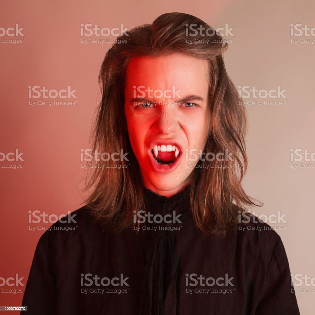 Gothic Halloween Clothes Young Spooky Count With Hairstyle Earl With Long Hair Vampire Man With Sharp Fangs Spooky Outfit For Halloween Party Undead Count Vampire In Gothic Shirt Terrible Demon Stock Photo