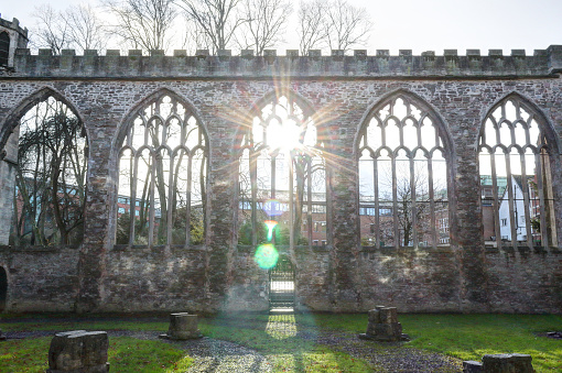 Gothic pointed arch windows on a stone wall without roof in the abandoned rumbled Temple Church in Bristol, in a sunny winter day, in United Kingdom