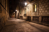 Spain, Barcelona, Gothic Quarter (Barri Gotic), Old Town, narrow street by night, historic city center