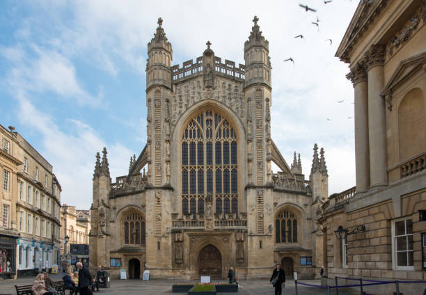 Gothic style Anglican church Bath Abbey, Bath, England Bath, England - Nov 5, 2018: Pigeons fly over the towers of Bath Abbey. roman baths england stock pictures, royalty-free photos & images