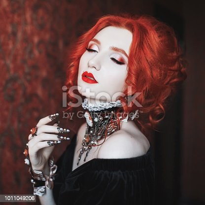 istock Gothic woman is a vampire with pale skin and red hair in a black dress and a necklace on her neck. Girl witch with vampire claws and red lips. Gothic look. Outfit for halloween. 1011049206