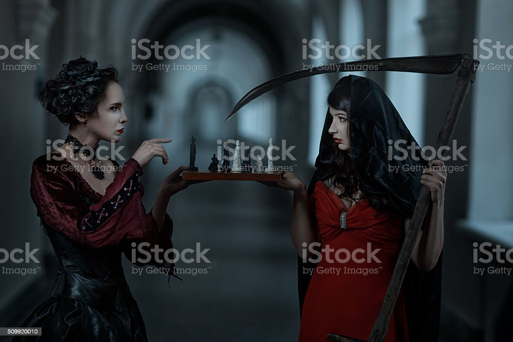 Gothic woman playing with death. stock photo