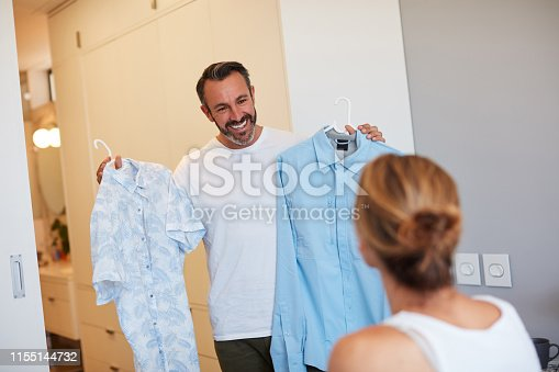 Cropped shot of a handsome mature man asking his wife's opinion on which shirt to wear