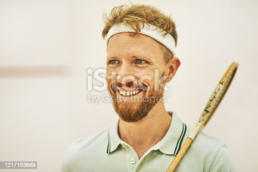 Shot of a confident young man standing on a squash court
