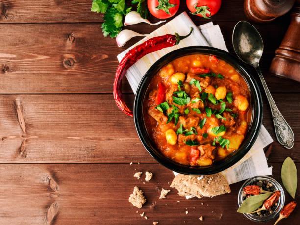 goulache dans un bol en céramique sur fond en bois. soupe hongroise traditionnelle. - hongrie photos et images de collection