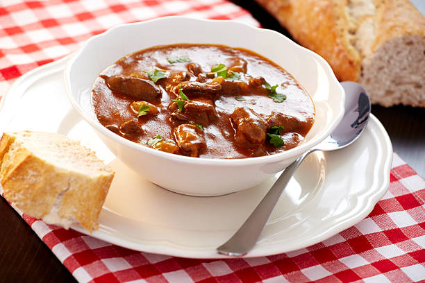 Goulash Delicious goulash served with fresh baguette goulash stock pictures, royalty-free photos & images