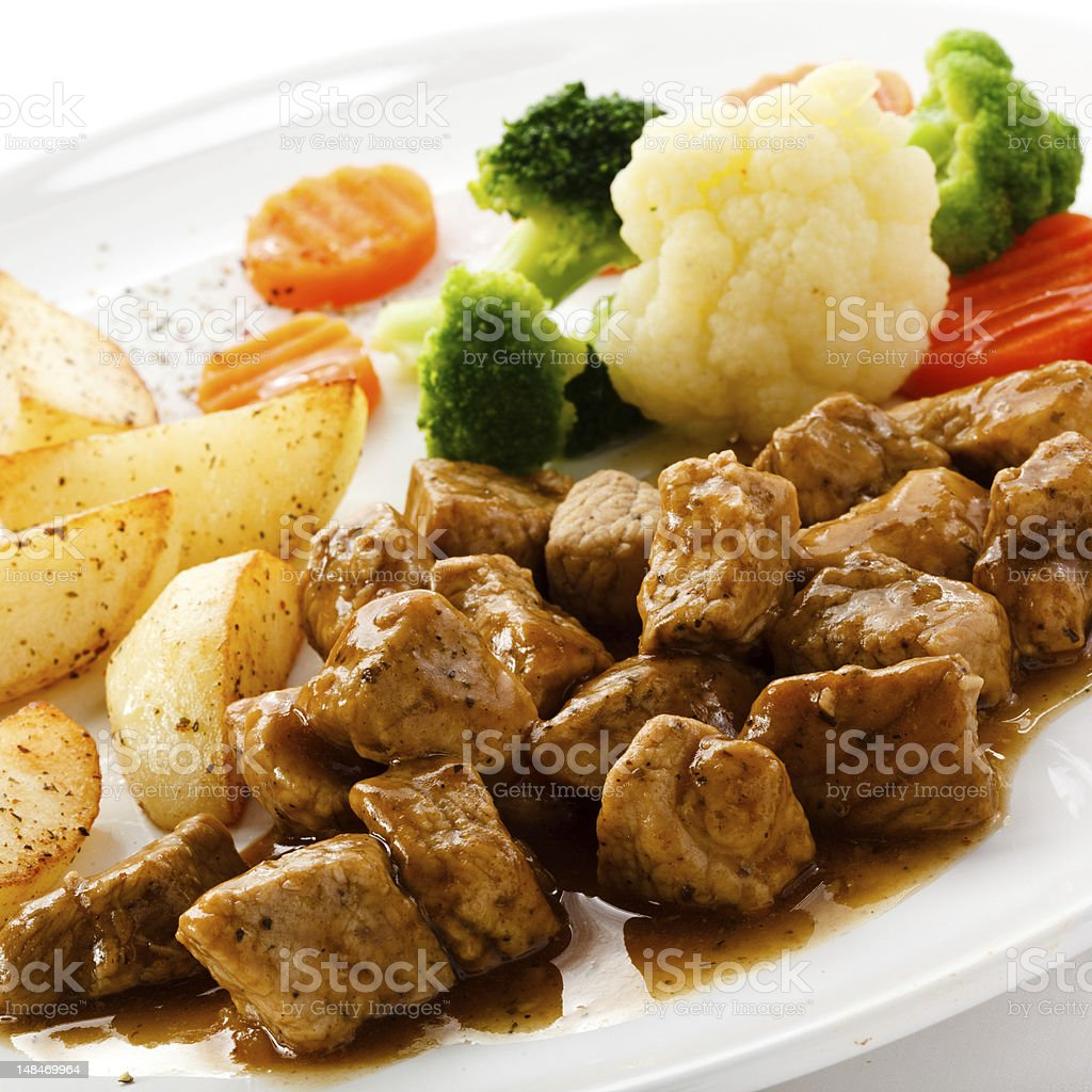 Goulash, roasted potatoes and vegetables royalty-free stock photo