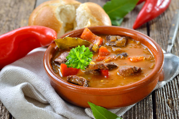 Goulash soup Hot Hungarian goulash soup served in a ceramic bowl with a fresh roll goulash stock pictures, royalty-free photos & images