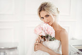 Classical young gourgeous bride. Studio interior fashion shot of fashion model in wedding dress with bouquet of flowers sitting in white room. Blonde woman portait with profeshional make-up and hairstyle.
