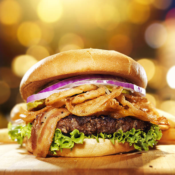 gourmet bacon hamburger with onion straws close up ohoto of a gourmet bacon hamburger with golden background and copy space composition. Burger has fresh onions, fried onion straws, lettuce, bacon and pickles. bacon cheeseburger stock pictures, royalty-free photos & images