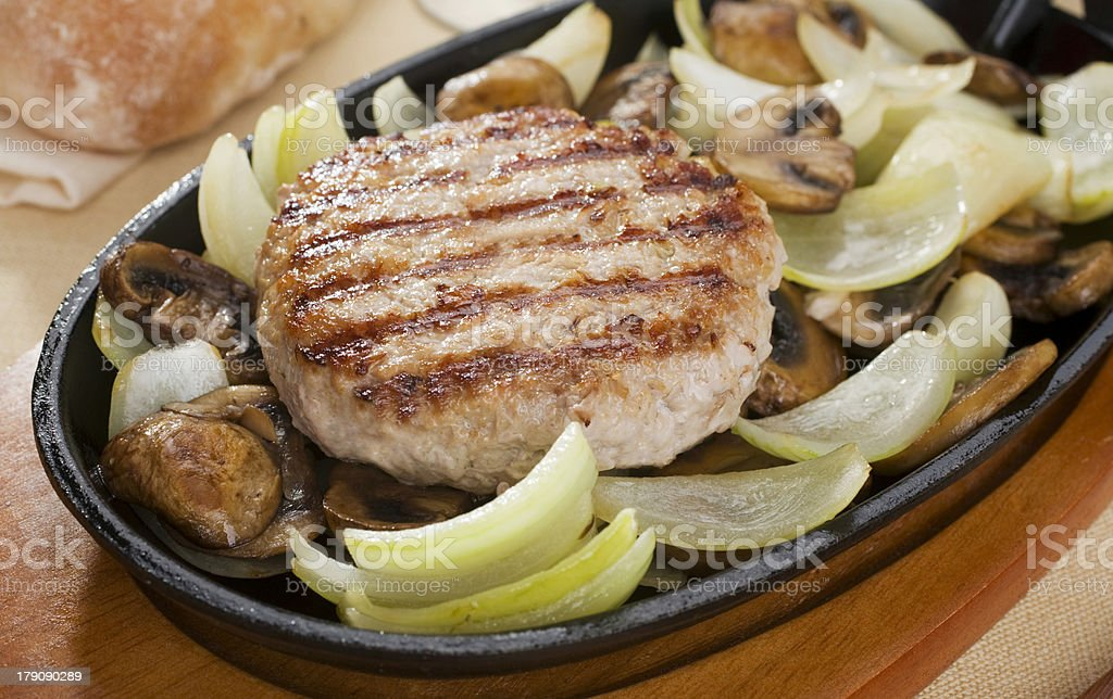 Gourmet Burger on a Sizzle Platter with Vegetables royalty-free stock photo