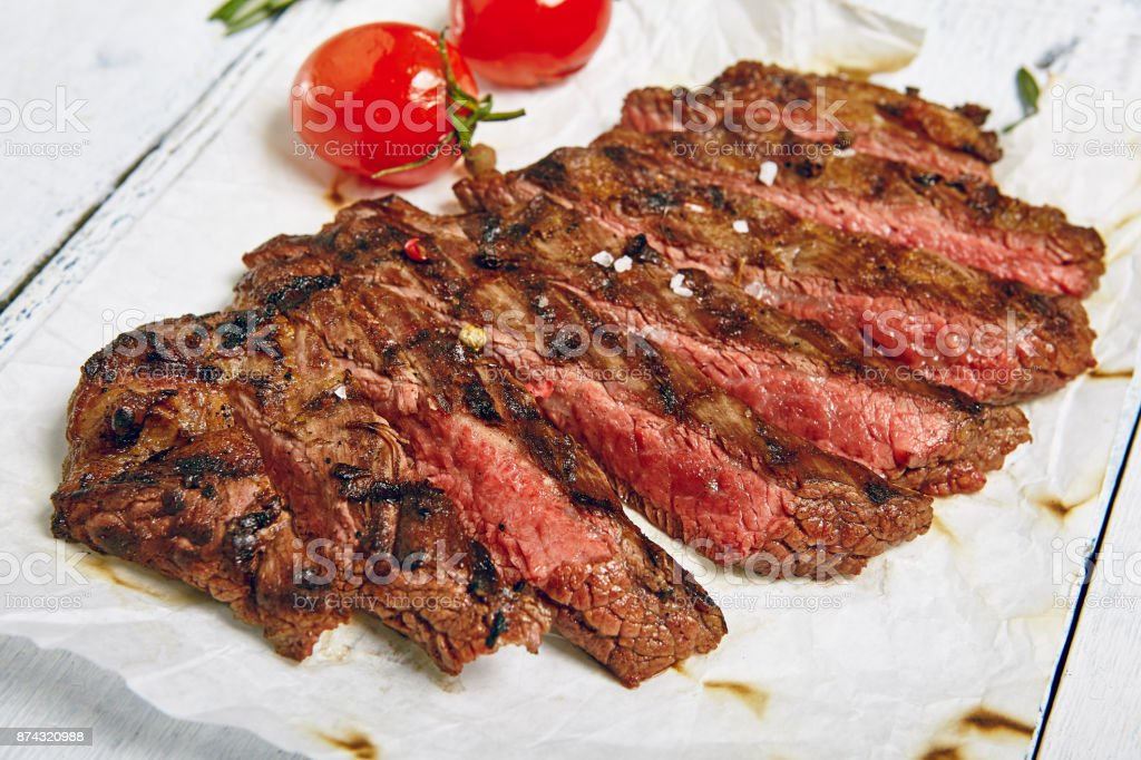 Gourmet Grill Restaurant Beef Steak Menu - Flank Steak on Wooden Background. Beef Steak Dinner stock photo