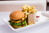 gourmet hamburger and fries with drinks on the side