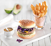 Gourmet hamburger and fries with avocado