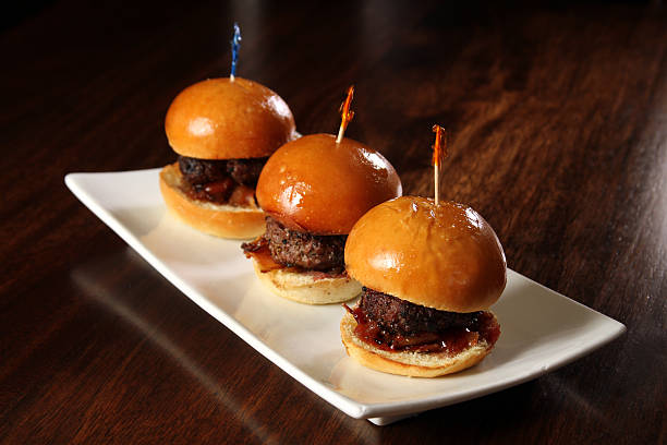 Gourmet hamburger sliders with bacon and copy space Gourmet hamburger sliders with bacon on white plate with toothpicks - room for copy, headline etc. slider burger stock pictures, royalty-free photos & images