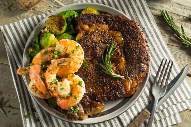 hausgemachten gourmet-steak und garnelen - steak anbraten stock-fotos und bilder