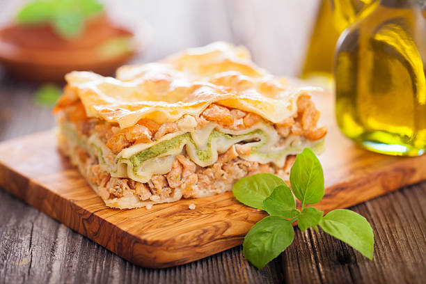Gourmet lasagna with glass of olive oil stock photo