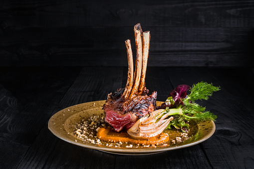 Gourmet Main Entree Course Grilled rack of lamb. Rack of lamb on a golden plate on a black background