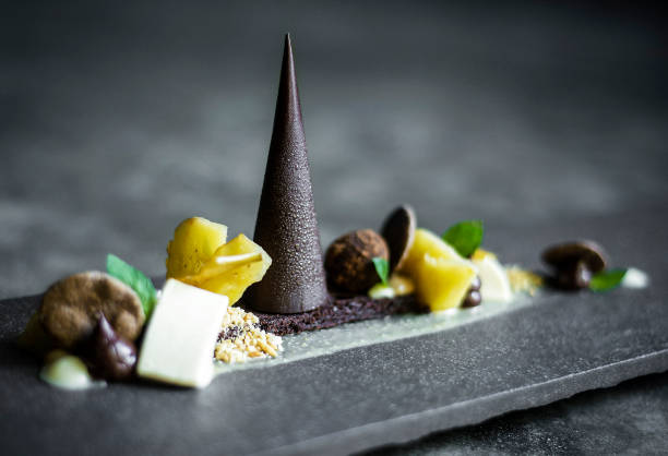 gourmet modern creative chocolate cake and dried fruit dessert dish on slate gourmet modern creative chocolate cake and dried fruit dessert dish on slate fine dining stock pictures, royalty-free photos & images