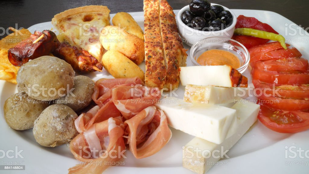 Gourmet platter of goat cheese, cured ham, sliced pizza, bread, sausage, potatoes, served with vegetables and red mojo sauce . stock photo